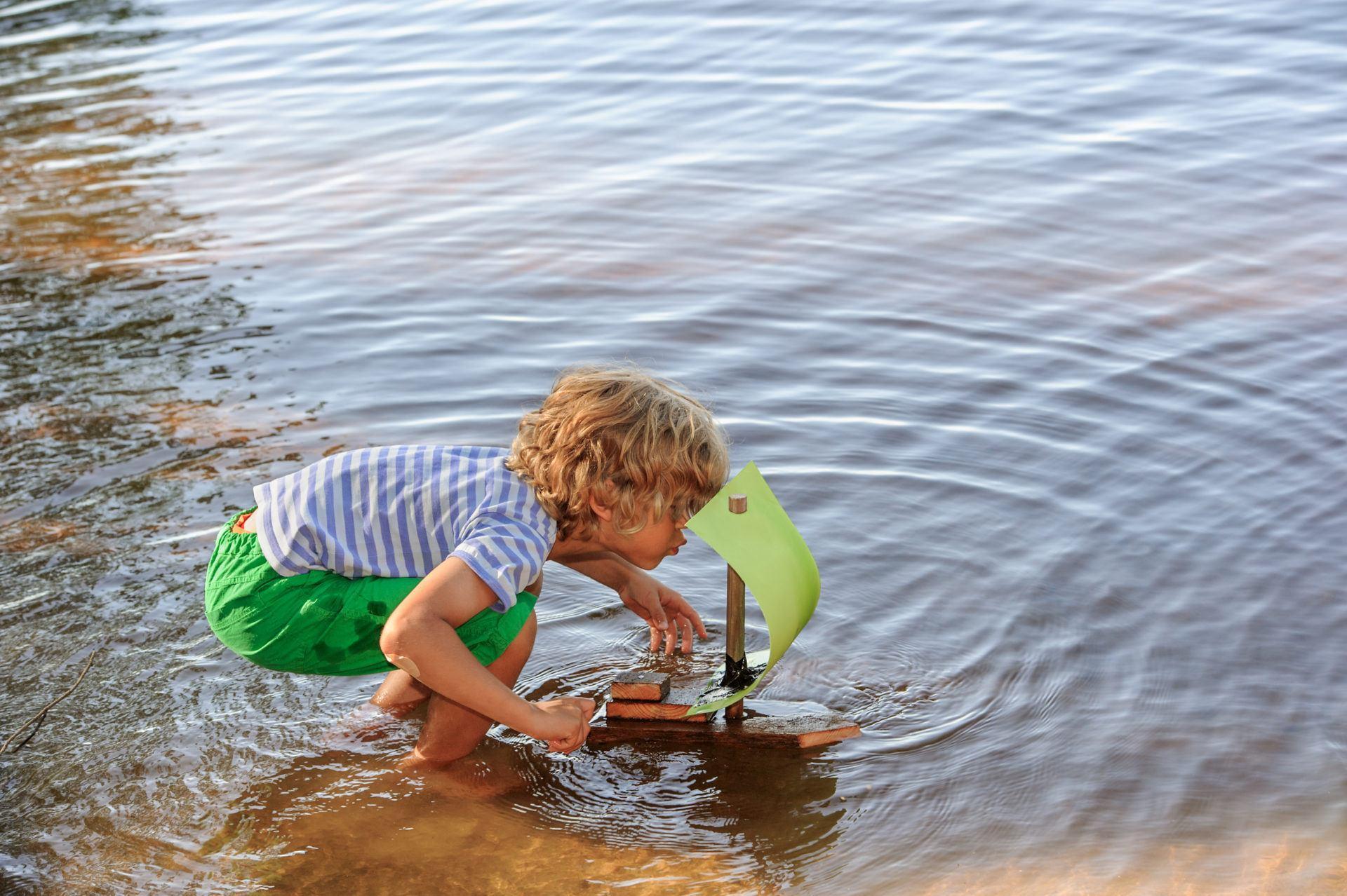poika puhaltaa tuulta itse tekemänsä veneen purjeisiin