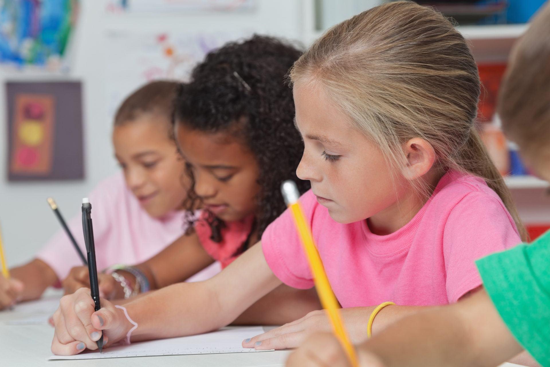 oppilaat kirjoittamassa