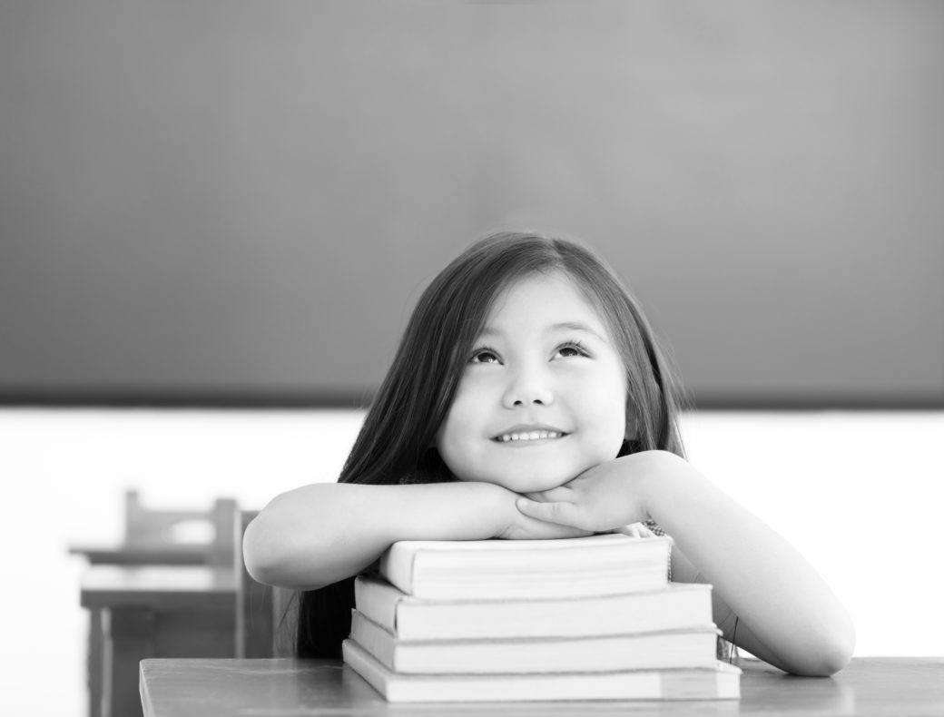 pieni tyttö ajattelee luokkahuoneessa kirjapinon päällä