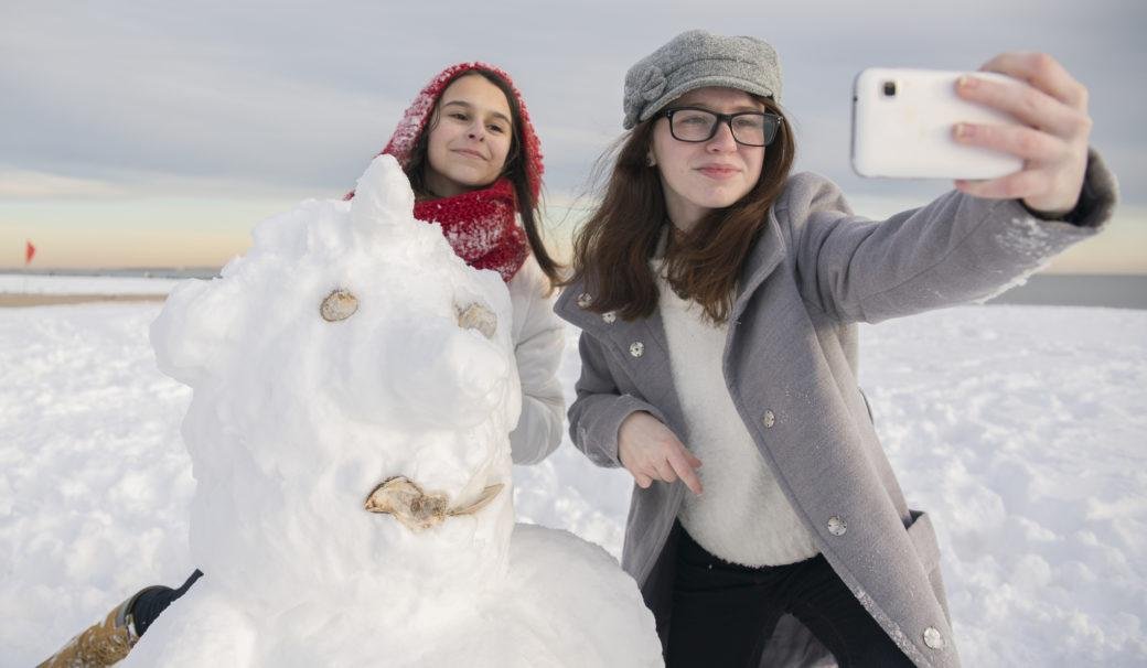 sisarukset ottaa selfieitä lumiukon kanssa